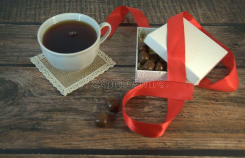 Una tazza di tè, una scatola bianca di cioccolato con un nastro rosso del raso su una tavola di legno immagini stock libere da diritti