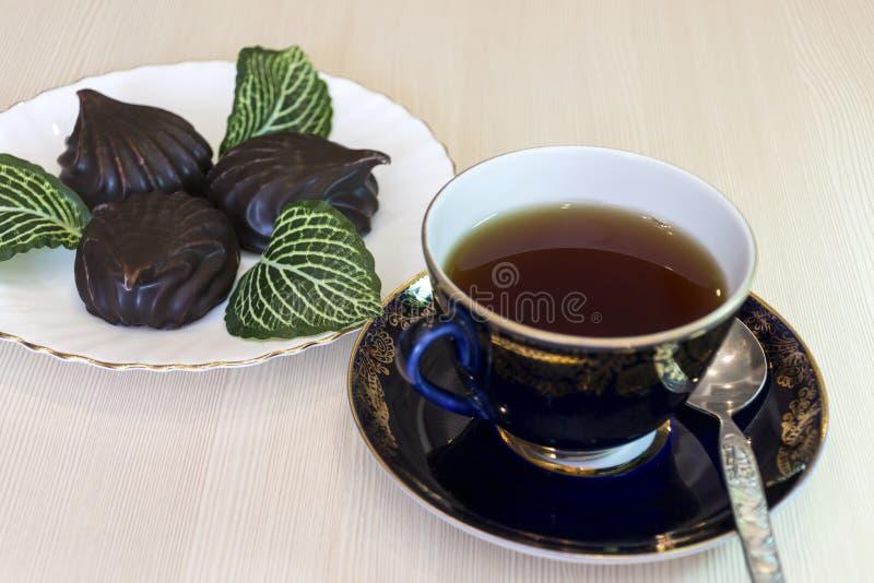 Una tazza di t? con le caramelle gommosa e molle in cioccolato immagine stock libera da diritti
