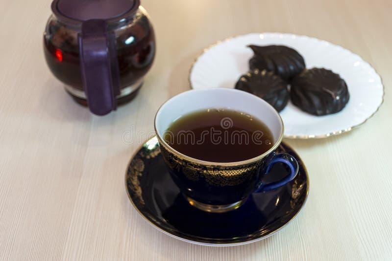 Una tazza di t? con le caramelle gommosa e molle in cioccolato fotografia stock libera da diritti
