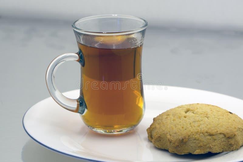 Una tazza di vetro di tè nero con i biscotti su un fondo di marmo grigiastro scuro, profondità di campo bassa Fondo della prima c immagini stock libere da diritti