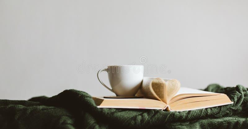 Una tazza e un libro con le pagine piegate in un cuore su una coperta tricottata accogliente fotografia stock libera da diritti
