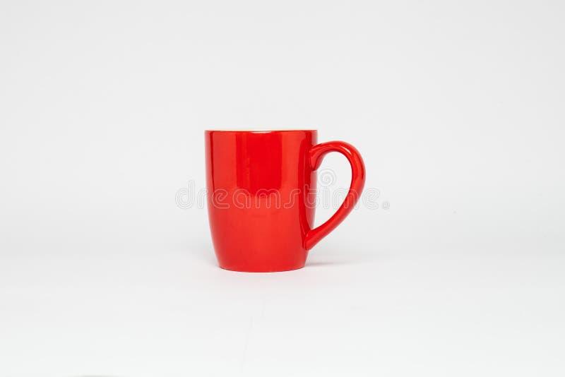 Una tazza rossa vuota isolata su bianco immagine stock