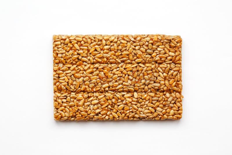 Una teja de oro grande de las semillas de girasol, una barra en una melaza dulce en un fondo blanco Dulces útiles y sabrosos de K fotografía de archivo libre de regalías