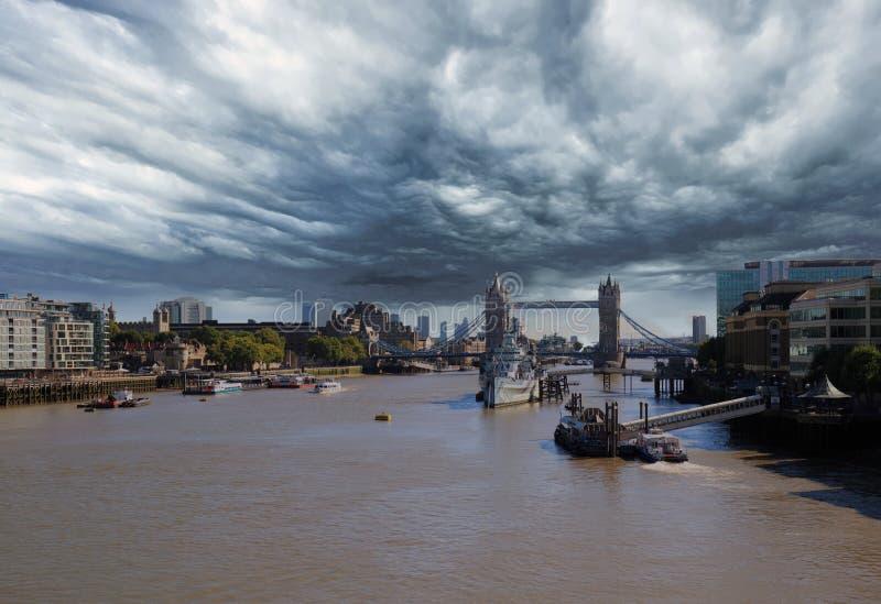 Una tempesta si rannuvola il Tamigi con il ponte della torre nei precedenti immagine stock
