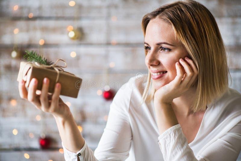 Una tenencia de la mujer joven envuelta regalo de Navidad fotografía de archivo libre de regalías