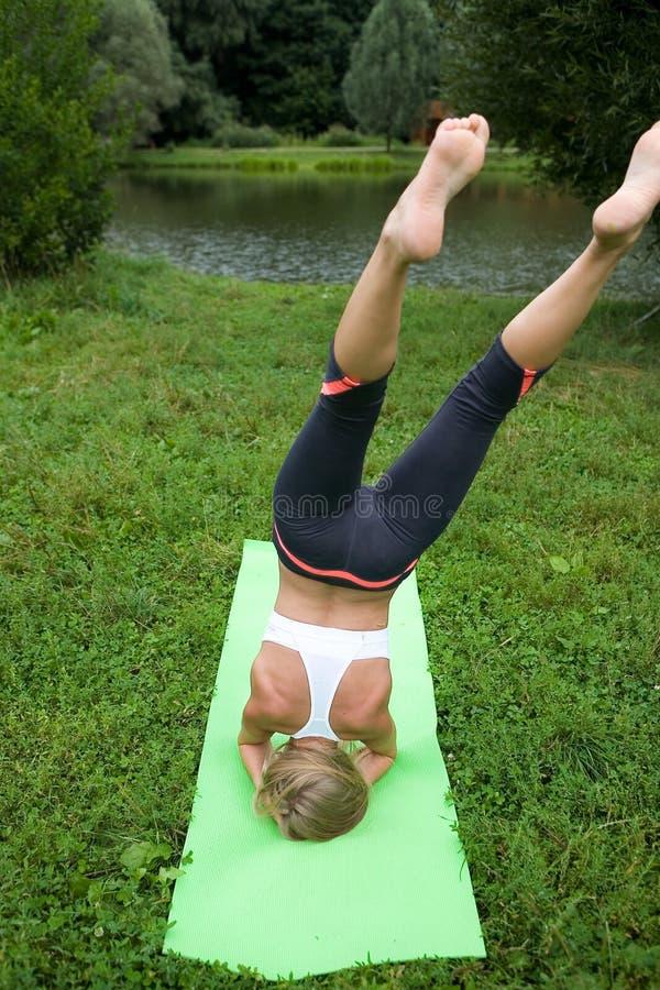 Una tentativa fracasada de una muchacha de realizar una actitud de la yoga fotografía de archivo