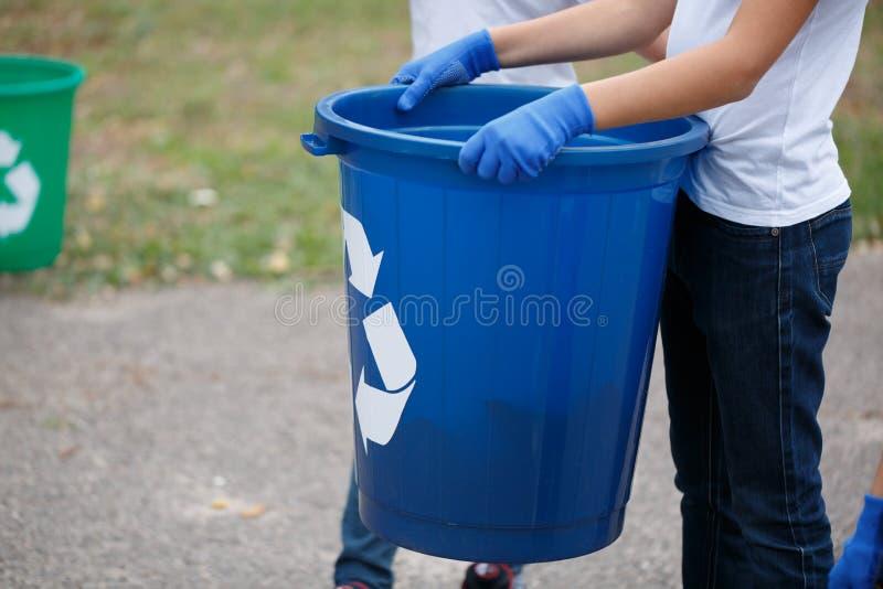 Una tenuta del piccolo bambino in mani un recipiente di riciclaggio blu su uno sfondo naturale vago Concetto di inquinamento di e fotografia stock libera da diritti