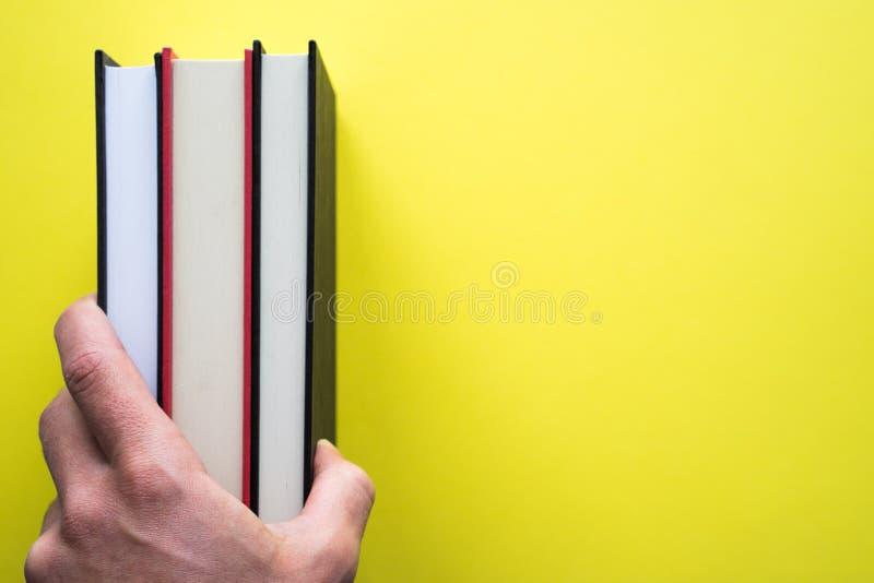 Una tenuta della mano prenota su un fondo giallo fotografia stock libera da diritti