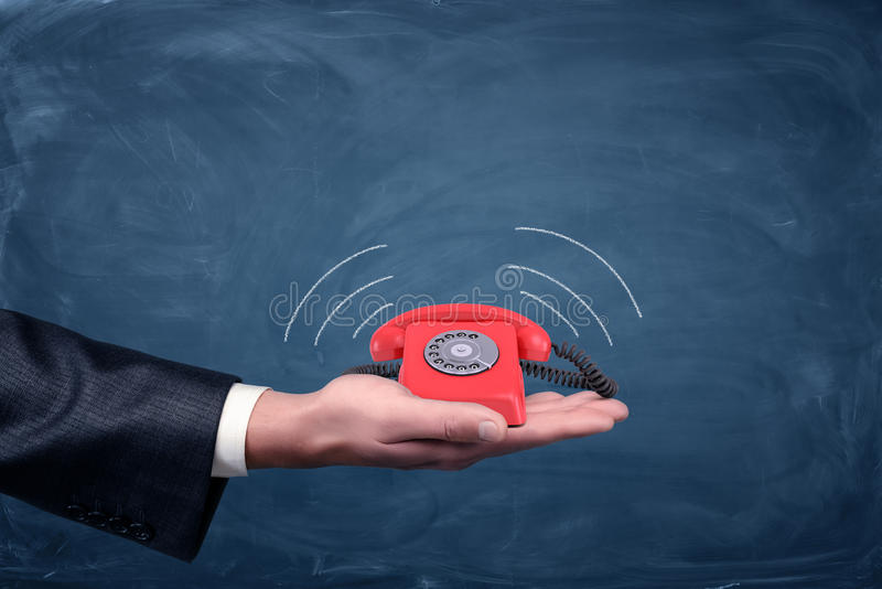 Una tenuta della palma del ` s dell'uomo d'affari un piccolo retro telefono di quadrante rosso con le linee che mostrano le emiss immagini stock