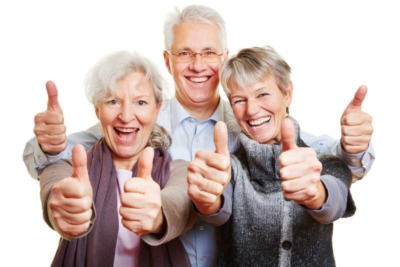 Una tenuta senior felice di tre genti fotografia stock libera da diritti
