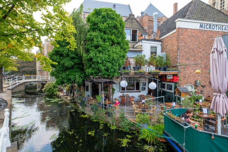 Una terraza acogedora en el agua y un barco de la terraza en el canal en t fotografía de archivo