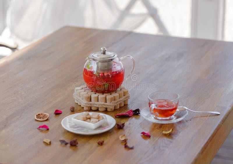 Una tetera de cristal con té brillante de la baya al lado de un vidrio del té, de una placa con el azúcar marrón, y de las frutas foto de archivo