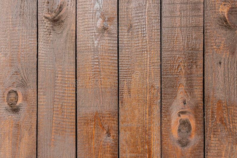Una textura de tableros marrones con los nudos y de la resina pintada con la impregnación para la madera imagen de archivo libre de regalías