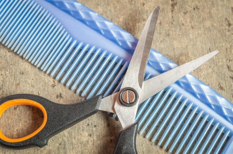 Una tijera y un peine azul en la parte superior de una mesa de madera gris texturada fotos de archivo libres de regalías