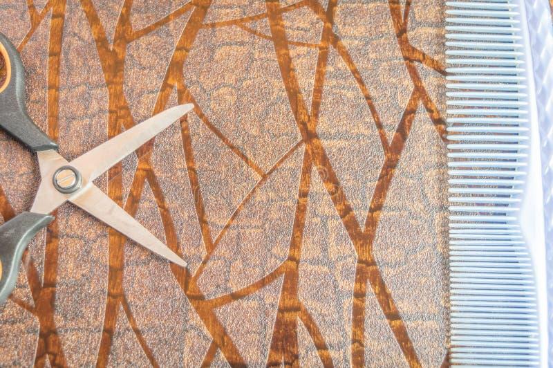 Una tijera y un peine azul en la parte superior de una mesa de madera texturizada imágenes de archivo libres de regalías