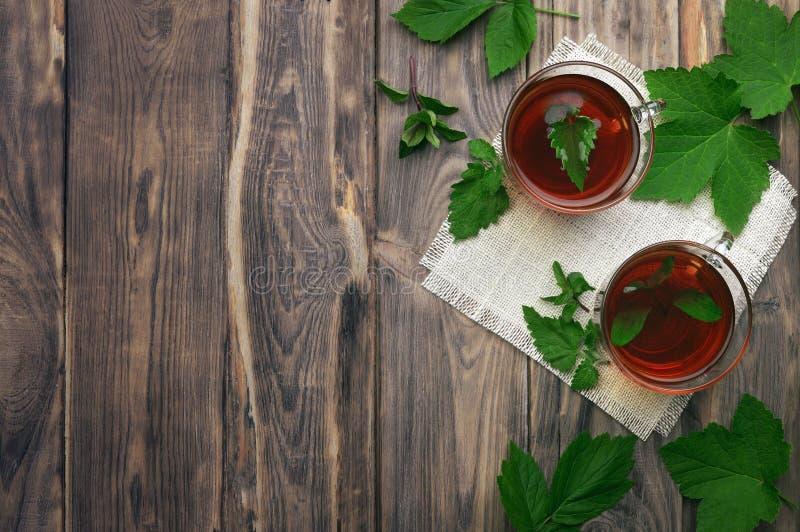 Una tisana fragrante con le foglie di menta, la melissa, i lamponi e l'uva passa Primo piano Una tazza di tisana su un fondo di l immagini stock