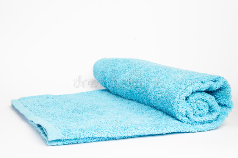 Una toalla azul rodó para arriba en un fondo blanco fotografía de archivo