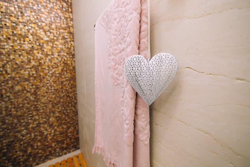 Una toalla rosada se seca en el cuarto de baño en el carril de toalla heated fotos de archivo