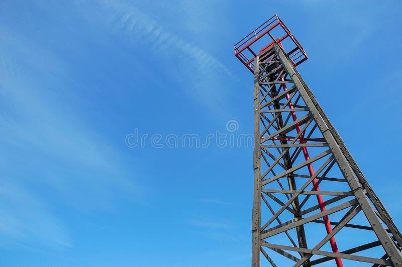 Una torre contro un cielo blu e soleggiato immagine stock