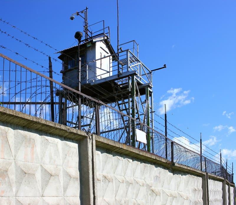 Una torre de la prisión con una cerca y un alambre de púas concretos fotos de archivo libres de regalías