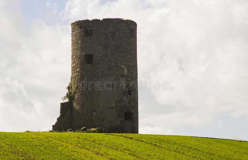 Una torre de piedra vieja del origen desconocido al fotógrafo en un campo del heno del corte en una granja cerca de Kircubbin en  fotografía de archivo libre de regalías