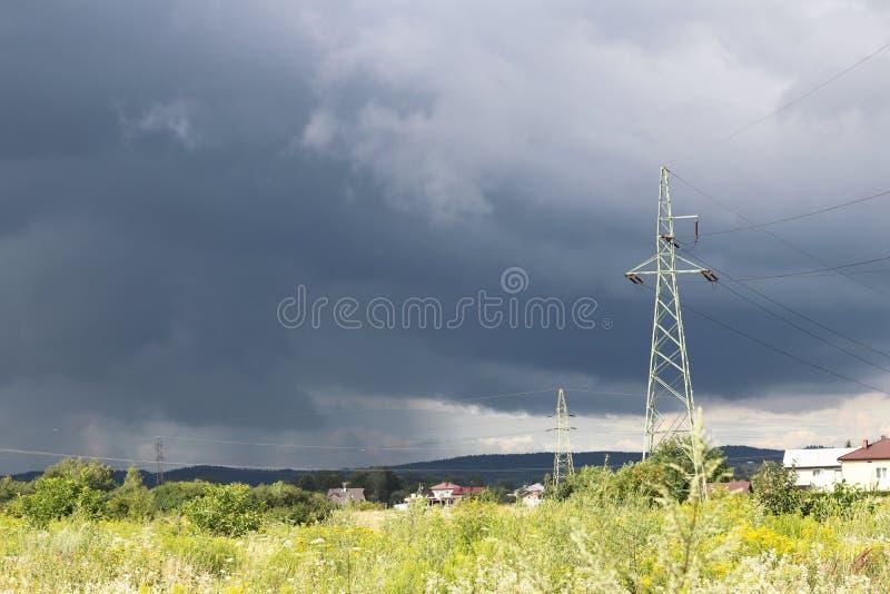 Una torre del metallo di una linea ad alta tensione di electrotransfers nei precedenti di un cielo tempestoso dopo una pioggia Ph fotografie stock libere da diritti
