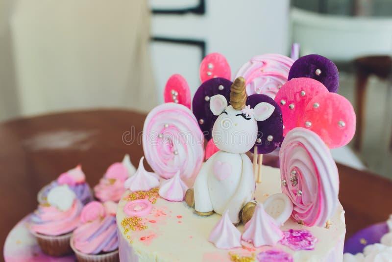 Una torta brillante hermosa adornada bajo la forma de unicornio de la fantas?a en el estante para libros azul El concepto de un p foto de archivo libre de regalías