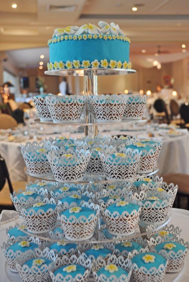 Una torta de boda con gradas de las magdalenas magníficas del Frangipani foto de archivo