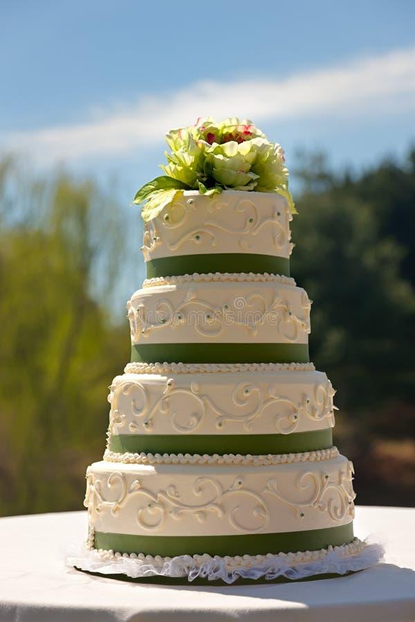 Una torta de boda de 4 gradas en una configuración del jardín foto de archivo