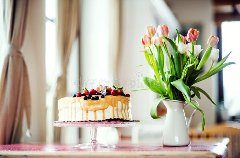 Una torta de cumpleaños en un soporte de cristal y un florero con los tulipanes en la tabla imagenes de archivo