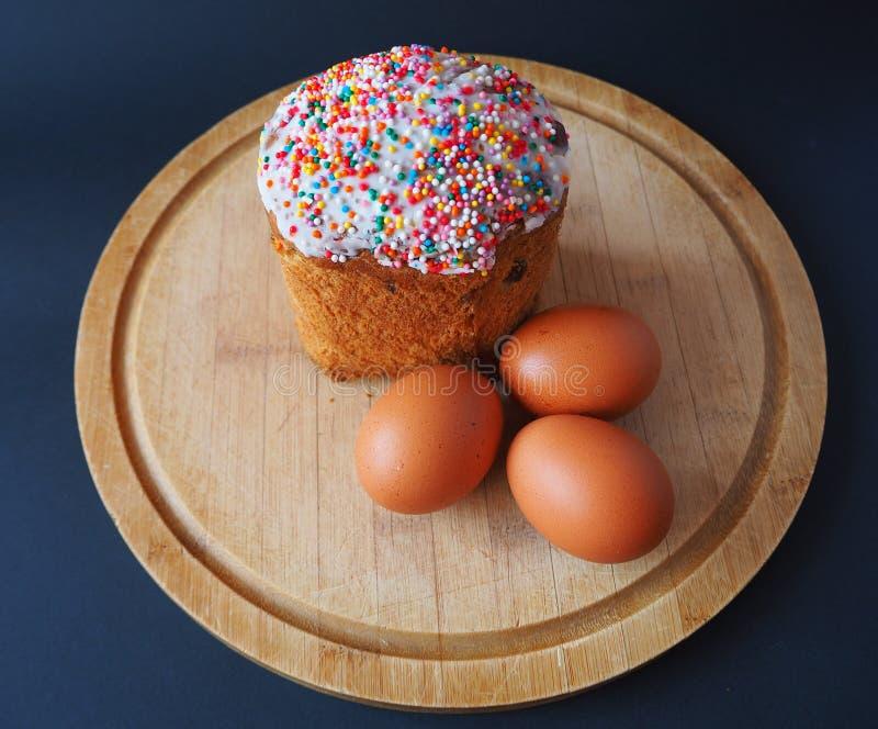 Una torta de pascua con los huevos en el tablero de madera fotografía de archivo