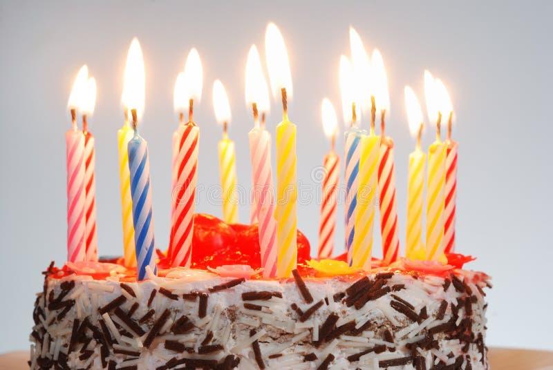 Una torta di compleanno con le candele illuminate fotografia stock libera da diritti