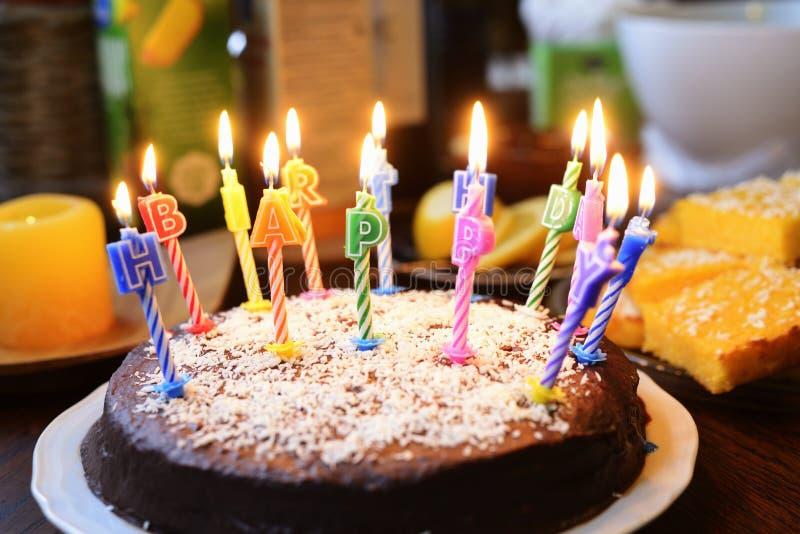 Una torta di compleanno con le candele illuminate immagini stock