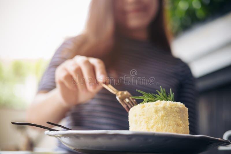 Una torta di formaggio asiatica del taglio manuale del ` s della donna con la forcella immagini stock libere da diritti