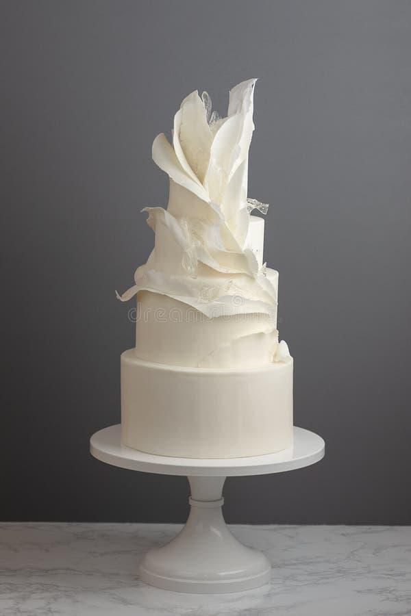 Una torta nunziale d'avanguardia di 4 file decorata con le increspature e lo zucchero tirato immagini stock libere da diritti