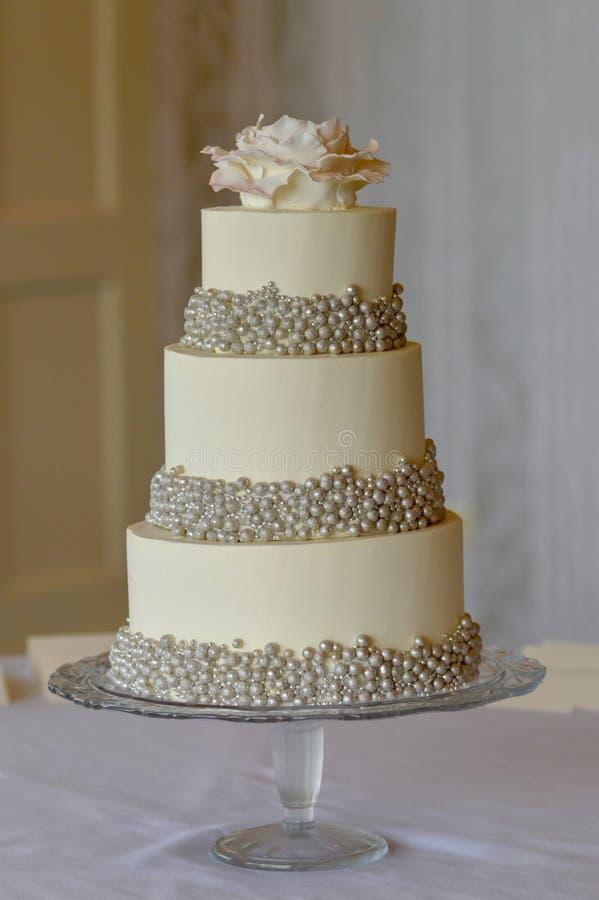 una torta nunziale di 3 file con le perle d'argento ed il fiore rosa commestibile a fotografie stock