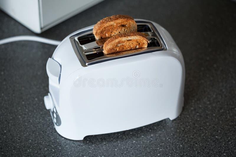 Una tostadora con las rebanadas de pan fotografía de archivo libre de regalías