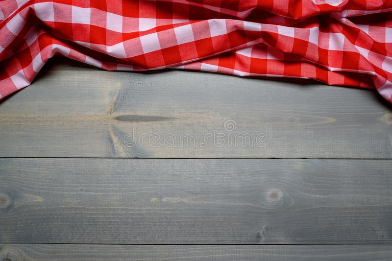 Una tovaglia controllata di picnic del percalle sulla vecchia vista di legno del piano d'appoggio fotografia stock