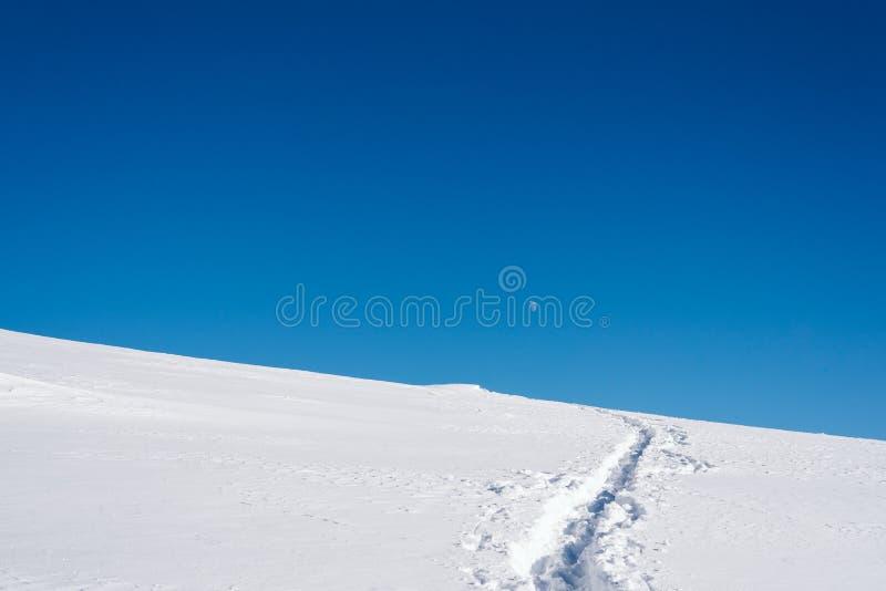 Una traccia su un pendio nevoso sopra una montagna con un chiaro cielo blu un giorno soleggiato fotografia stock libera da diritti