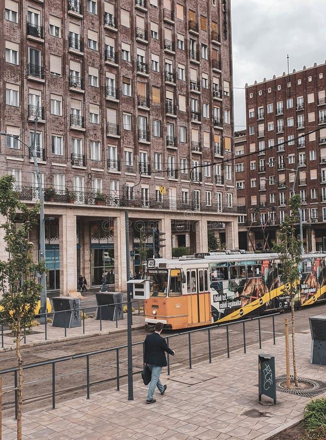 Una tranvía amarilla que pasa cerca en uno de los distritos del quintal de Budapest, Hungría foto de archivo