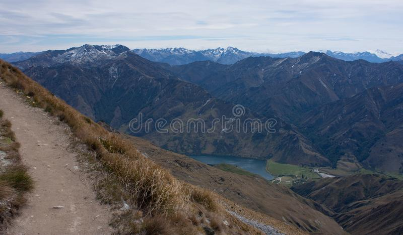 Una trayectoria que lleva al top de Ben Lomond cerca de Queenstown en Nueva Zelanda, montañas en el fondo imagenes de archivo