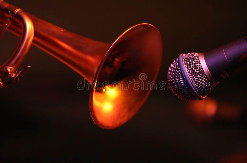 Una trompeta y un micrófono en la posición del primer imagen de archivo