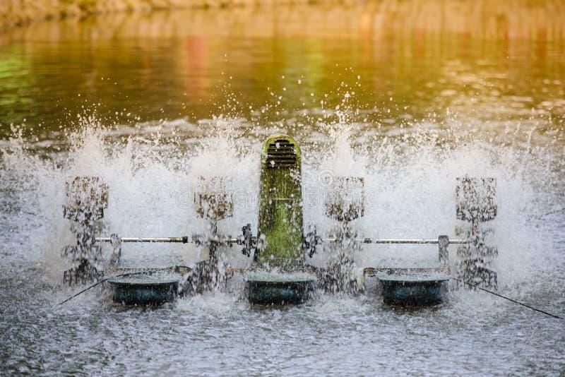 Una turbina dell'acqua sta funzionando in uno stagno immagini stock