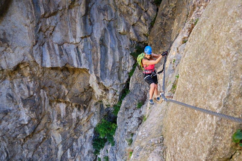 Una turista che attraversa una sezione via ferrata della turda gorge Cheile Turzii Romania, con una roccia impressionante sul ret immagine stock