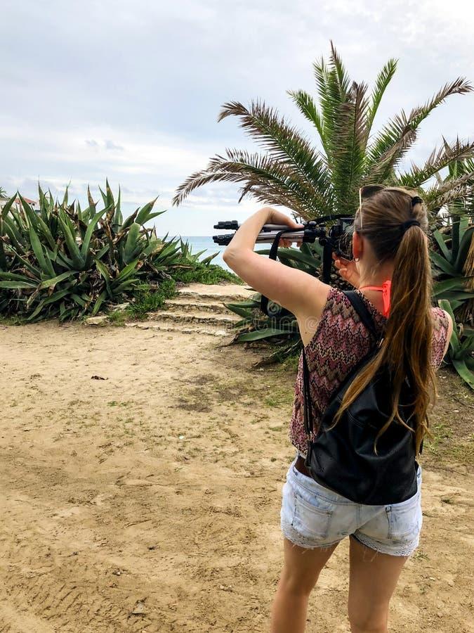 Una turista sostiene en su mano una cámara con un trípode y fotografía el paisaje marino, vista desde atrás. Paisaje marino ve imágenes de archivo libres de regalías
