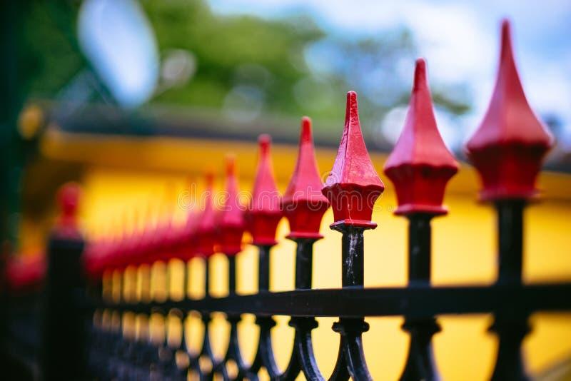 Una valla de seguridad rematada roja del hierro labrado fotos de archivo