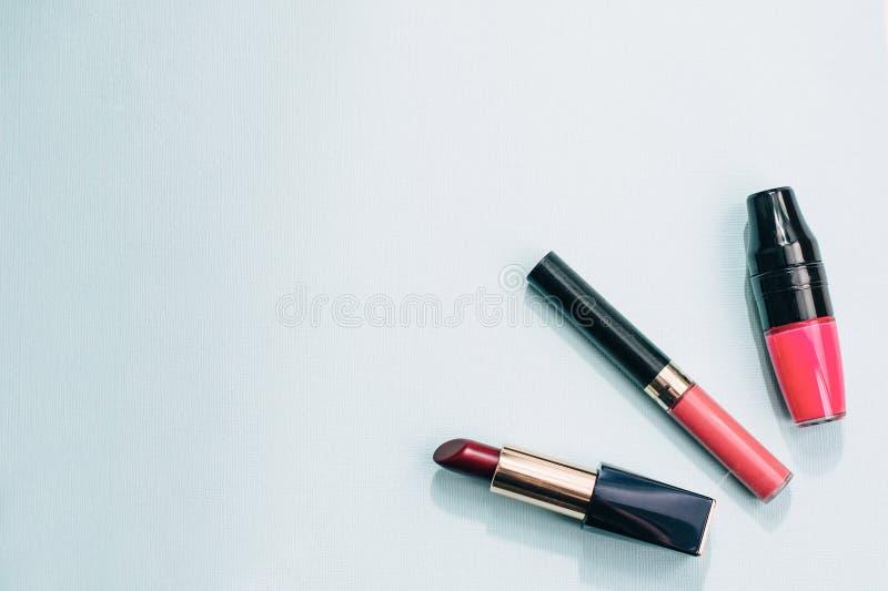 Una variedad de barra de labios, lustre en un fondo azul en colores pastel imagen de archivo libre de regalías
