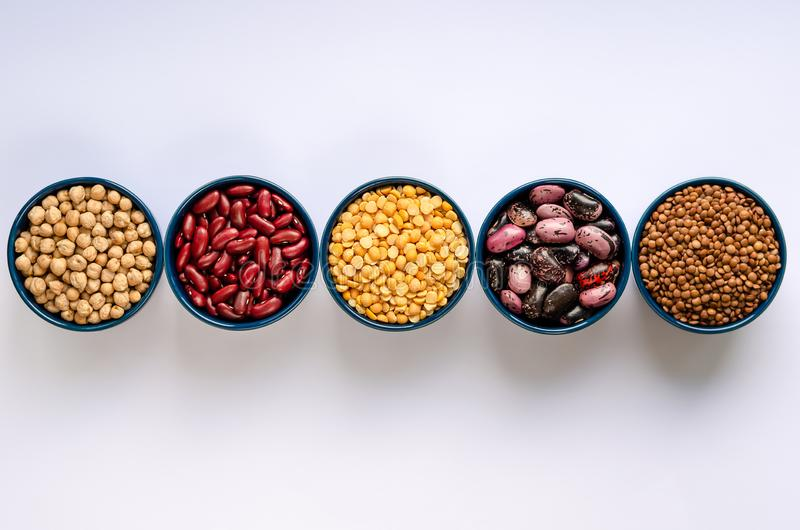 Una variedad de legumbres Lentejas, garbanzos, guisantes y habas en cuencos azules en un fondo blanco Visi?n superior foto de archivo