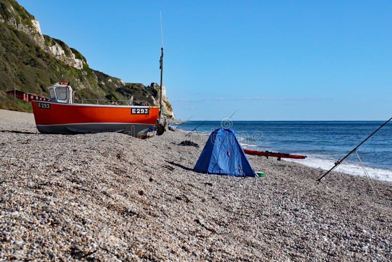 Una vecchia barca sulla spiaggia a Branscombe in Devon, Inghilterra L'attrezzatura dei pescatori sta nella priorità alta fotografia stock