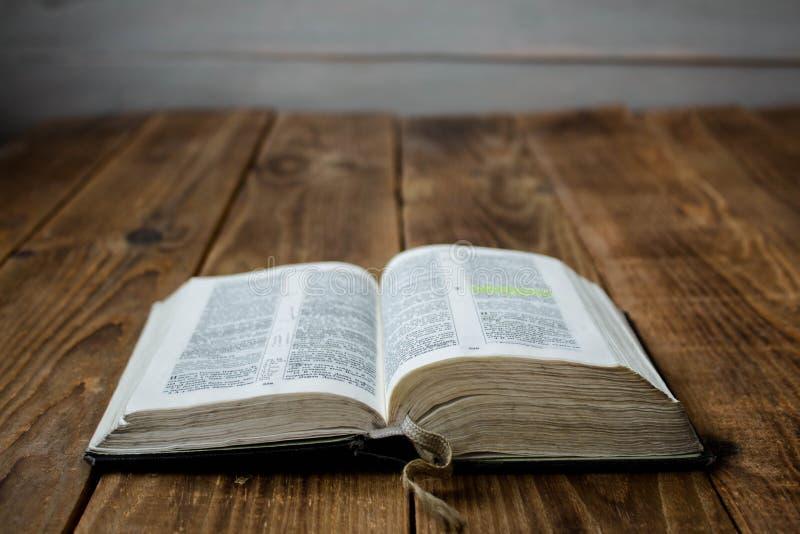 Una vecchia bibbia aperta su fondo di legno immagini stock libere da diritti